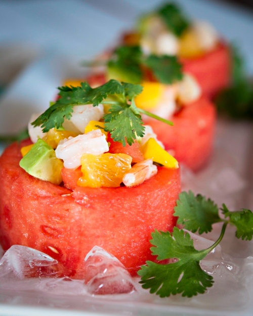 watermelon cups filled with fresh fruits salad topped with herbs are very refreshing