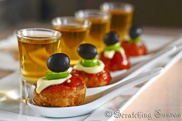 falafels on spoons with ketchup, cream cheese, jalapeno and olives on top
