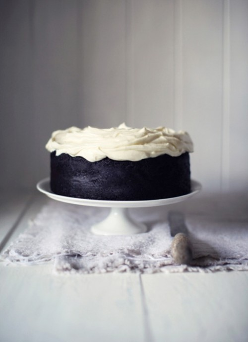 a black wedding cake with a white whipped cream top for a soft gothic wedding