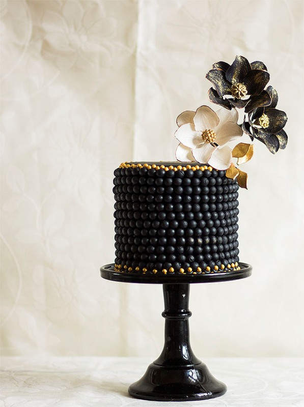 a black wedding cake decorated with beads and with black and white plus gold sugar blooms