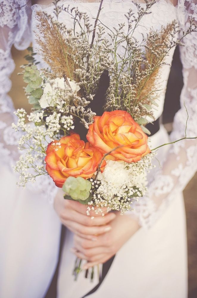 a fall boho wedding bouquet with orange blooms, baby's breath, dried elements and grasses plus some greenery