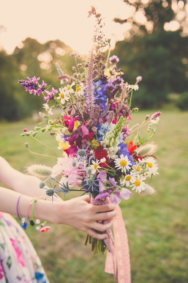 a super colorful boho summer wedding bouquet with pink, fuchsia, blue and red blooms and lots of textural greenery and grasses