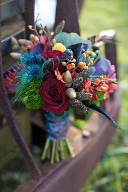 a colorful wedding bouquet in burgundy, blue, red, orange and purple, with feathers and acorns will fit a fall boho bride