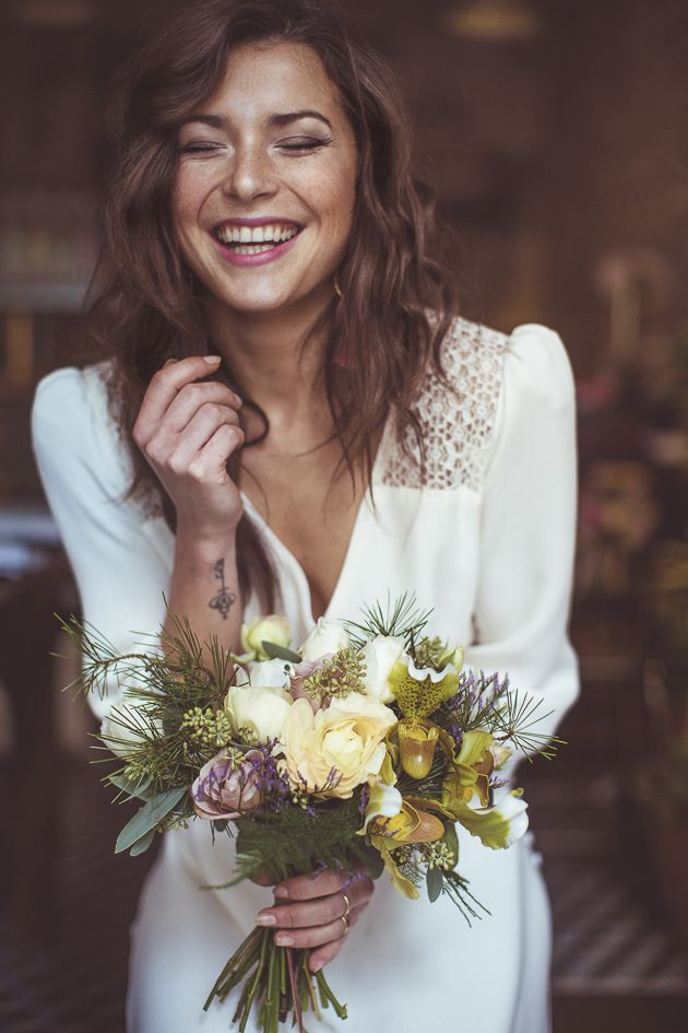 a pale wedding bouquet in white, lilac and green, with evergreens and usual greenery for a winter boho bride