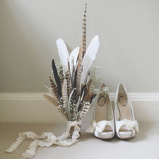 a boho wedding bouquet composed of feathers and baby's breath with a lace ribbon is a cool idea