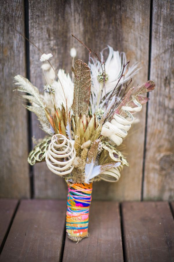 a bright summer wedding bouquet with feathers, curls and a very colorful wrap is a fun idea