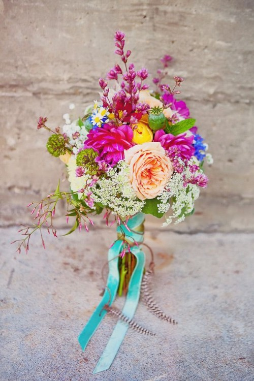 a colorful summer boho wedding bouquet with pink, peachy, white and blue blooms and some turquoise ribbons