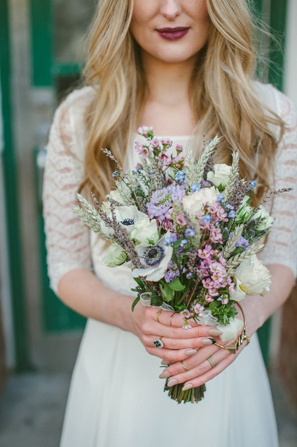 a pastel wedding bouquet of white and pastel blooms, of spikes and dried herbs,, with greenery