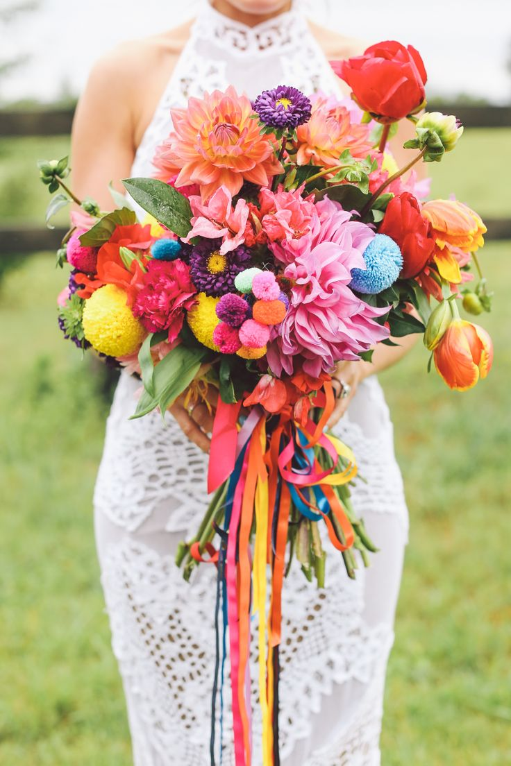 a colorful boho summer wedding bouquet in pink, red, orange, purple, with bright pompoms and colorful ribbons for a summer boho bride