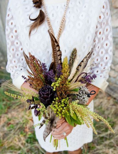 a fall wedding bouquet with deep purple blooms, green berries, feathers and dried spikes is great for a fall boho bride