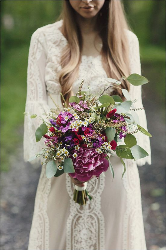 a bright summer boho wedding bouquet in purple, pink, white, with various kinds of blooms and greenery