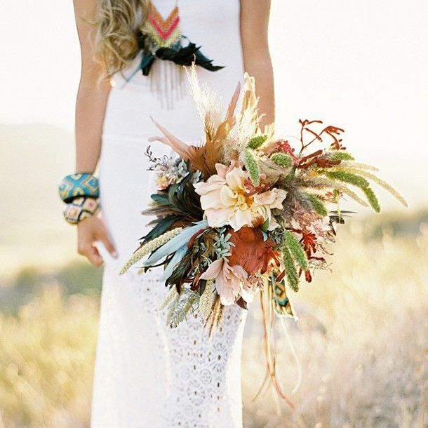 a textural boho wedding bouquet with pastel blooms, greenery, dried leaves and spikes plus feathers for a boho bride