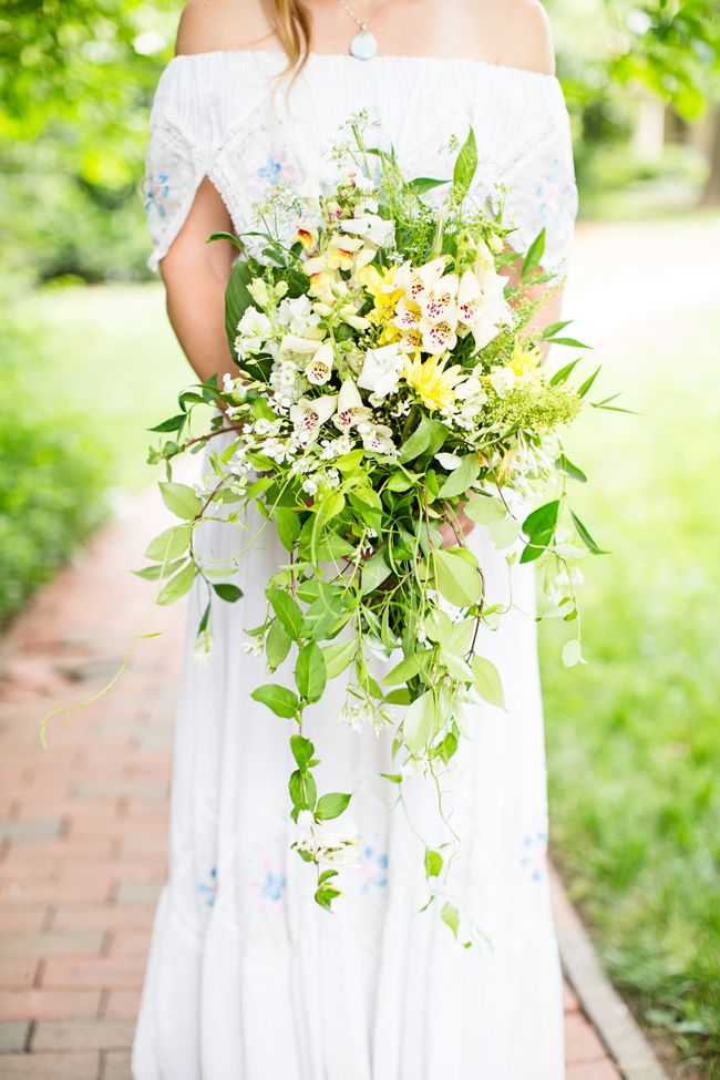 an oversized spring wedding bouquet of blush, yellow blooms and lots of greenery cascading down for a lush and bold boho look