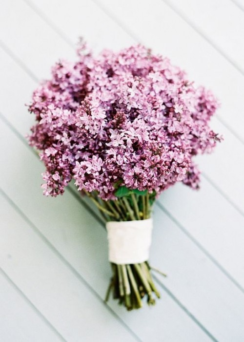 a lilac wedding bouquet with a white wrap is a simple and cool idea for a summer boho bride