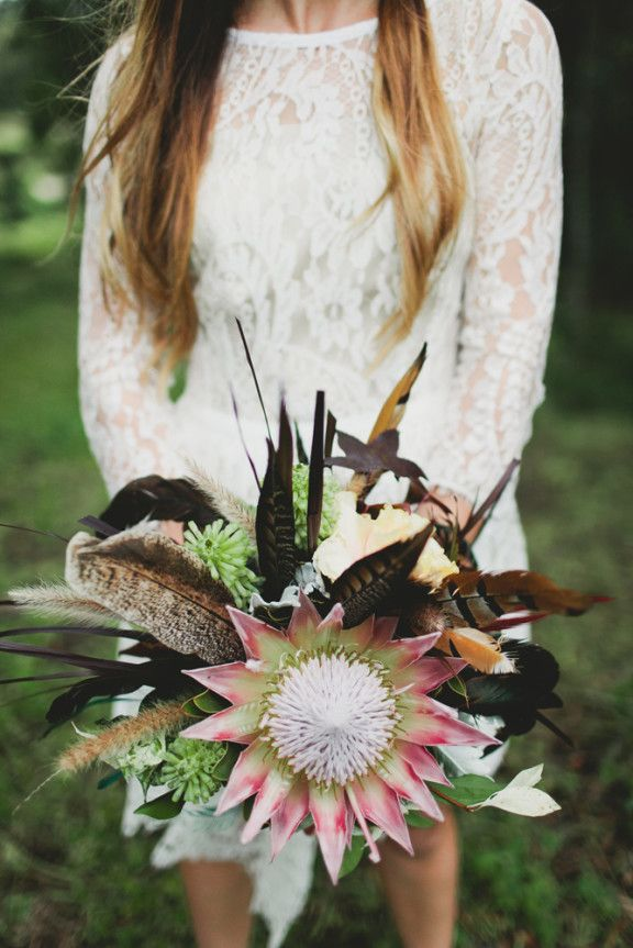 a fall boho wedding bouquet composed of succulents, feathers, spikes and king proteas looks bold