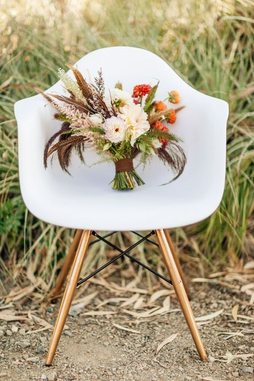 a bright fall boho wedding bouquet of neutral and orange blooms, greenery, feathers, dried touches and with a brown wrap