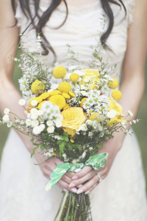 a bright summer boho wedding bouquet of white and yellow blooms, with greenery, billy balls and a simple green wrap