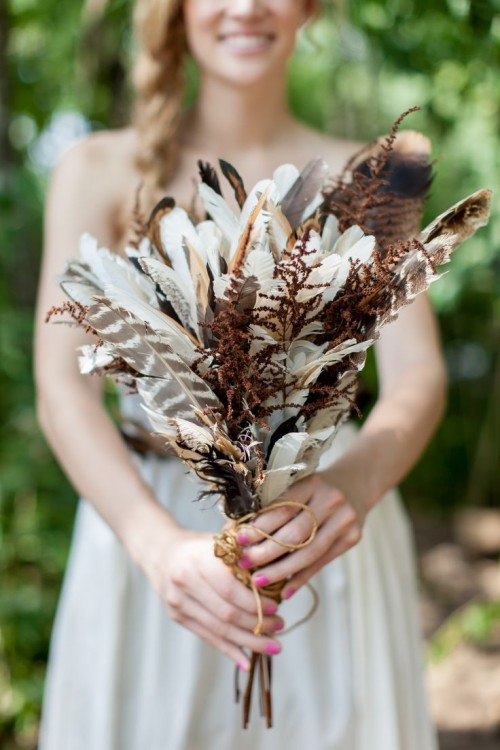 a boho wedding bouquet of feathers and dried elements is a cool idea for a fall boho bride