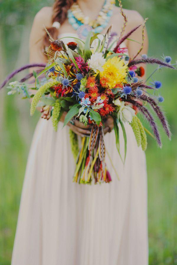 a colorful wedding bouquet of orange, yellow, blue, purple and other flowers plus various spikes and textural elements here and there