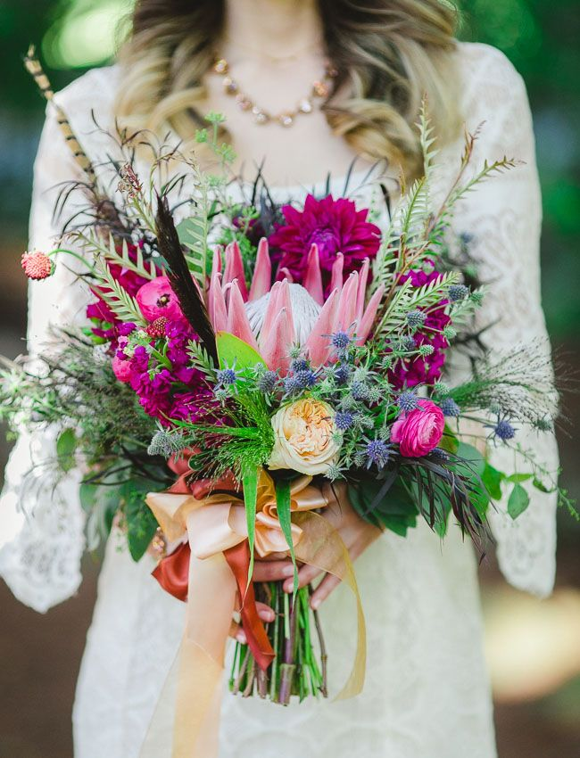 a bright wedding bouquet of pink and fuchsia blooms, thistles, feathers, spikes and lots of greenery to rock for a summer boho bride