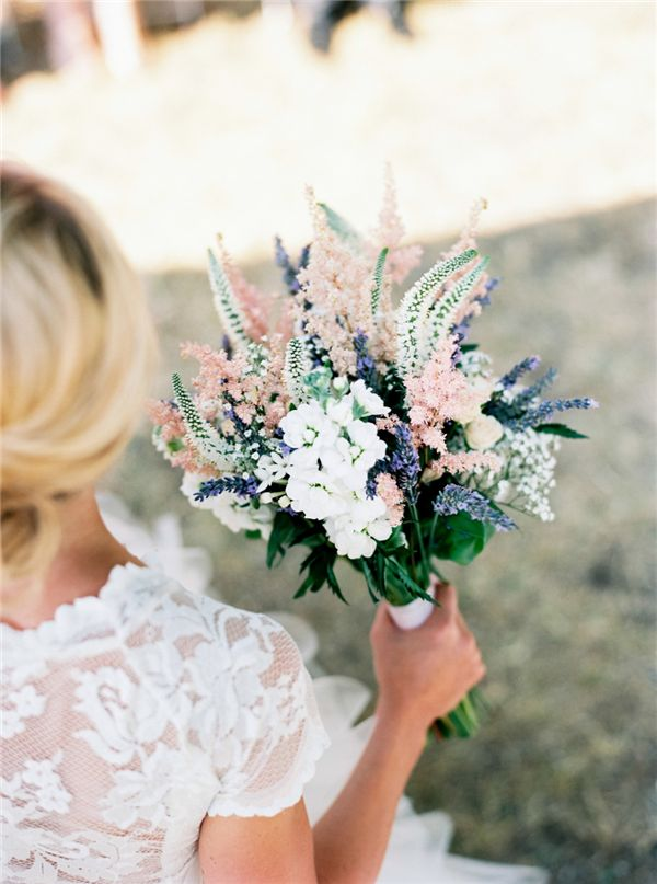 a pastel wedding bouquet in pink, blue and white with lots of greenery and other textural elements