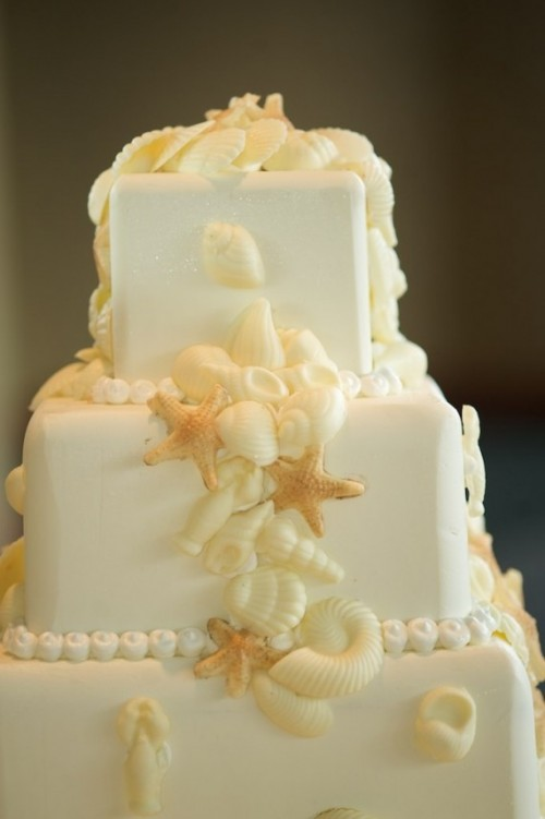 a white square wedding cake with seashells, starfish and pearls of sugar is a simple and elegant beach wedding cake