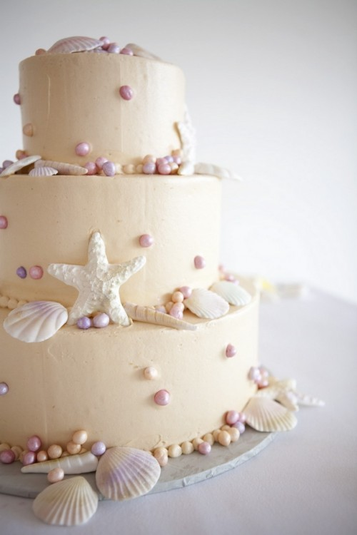 a tan textural wedding cake with pearls, seashells and starfish is a stylish wedding cake idea to try