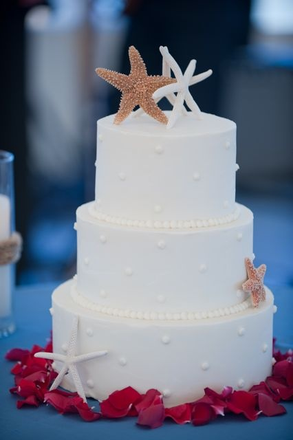 an elegant white wedding cake with dots, starfish of sugar for a stylish all white beach wedding