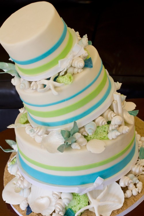 a bright wedding cake with colorful stripes, sugar seashells and starfish plus greenery looks fun and bold