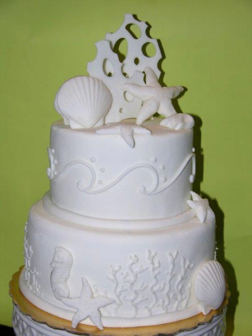 a white textural wedding cake with sugar seashells, starfish, corals and other stuff is a nice option for a white beach wedding