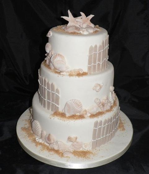 a neutral beach wedding cake with sugar fences, starfish, seashells and beach sand - everything edible