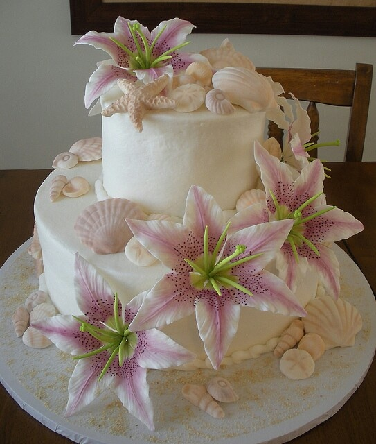 a white beach wedding cake with seashells, starfish of sugar and faux blooms for a beach tropical wedding
