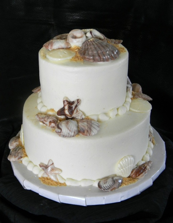 a white beach wedding cake with edible starfish, seashells, beach sand and pearls of chocolate is delicious