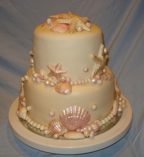 a neutral yet shimmering beach wedding cake with pink starfish and seashells, pearls and other sea creatures of sugar