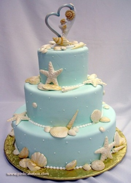 a blue beach wedding cake with pearls, seashells, starfish and a heart topper for a bright beach wedding
