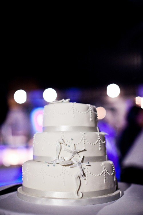 a super elegant white beach wedding cake with ribbons and sugar starfish and sea horses looks very chic and stylish