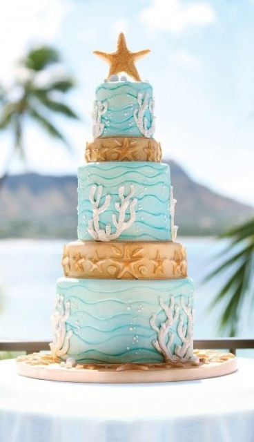 a bright beach wedding cake with light blue and tan tiers, bubbles, starfish, corals and other stuff for a creative and whimsy look