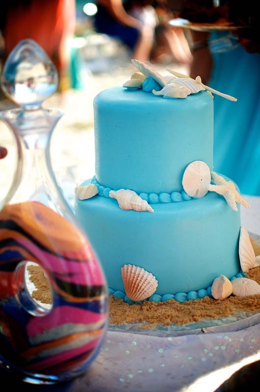 a bright blue wedding cake with seashells, real and sugar ones is all you need for a beach wedding