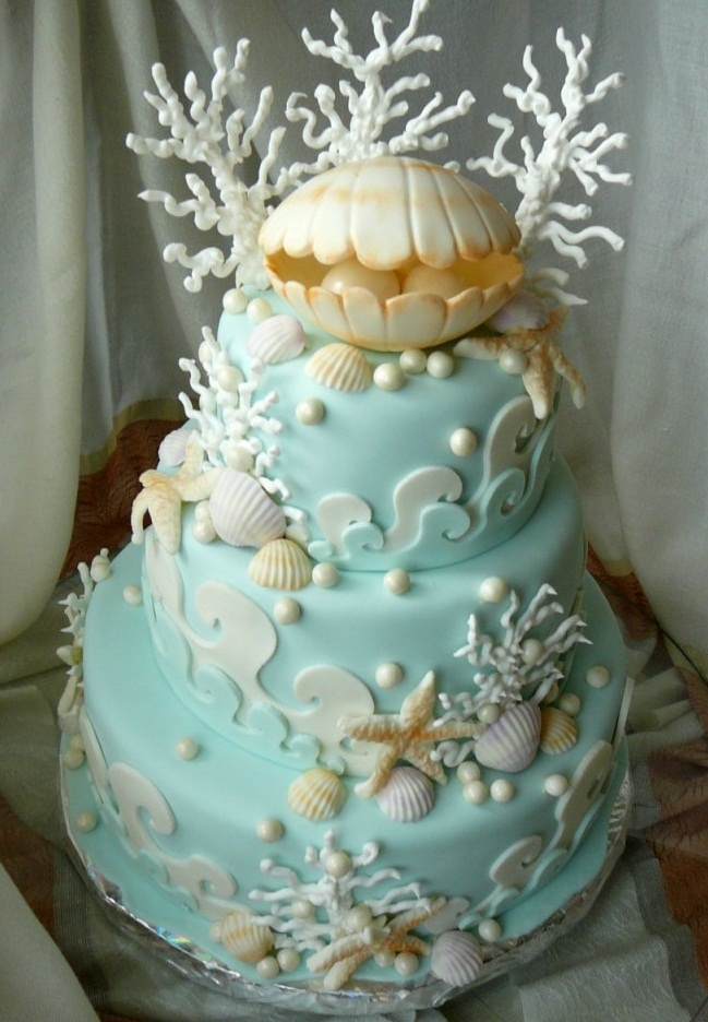 a whimsical beach wedding cake in light blue, with sugar waves, starfish, seashells, corals and a large shell on top