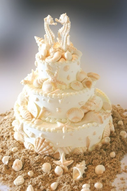 a neutral beach wedding cake decorated with sugar starfish, seashells and sea horses on top for a chic and catchy look