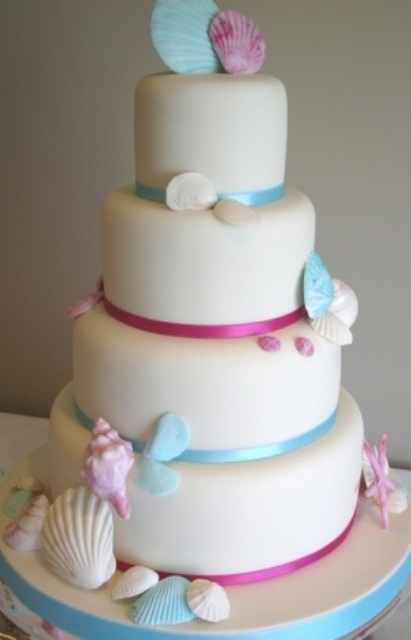 a plain white wedding cake with blue and pink ribbons, with pink and blue sugar seashells and starfish is a chic and fun idea for a beach wedding