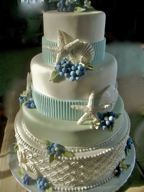 a shiny white wedding cake with light blue ribbons, sugar berries, starfish, patterns looks very quirky and unusual