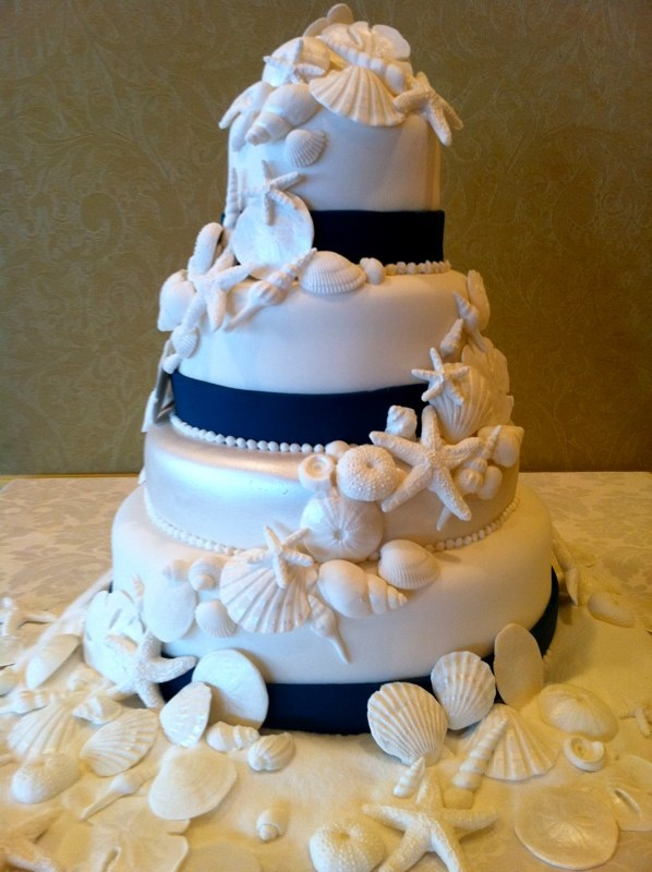 a nautical wedding cake in white, with navy ribbons, sugar seashells, starfish and urchins is very bold and contrasting