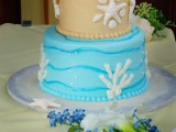 a bright beach wedding cake with a tan and bright blue tier, sugar corals, seashells and starfish for a beach wedding