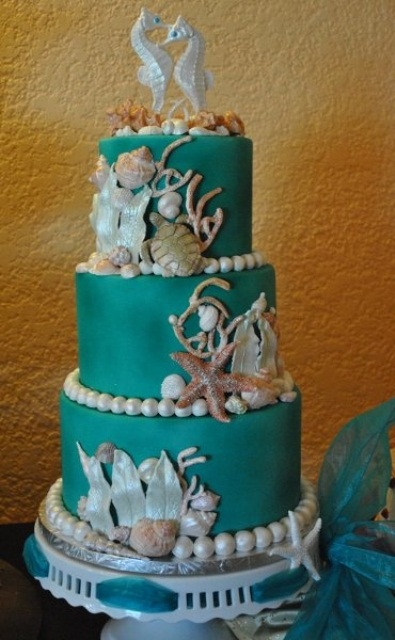 a green beach wedding cake with gorgeous sugar starfish, seashells, pearls, corals and sea horses on top is very chic