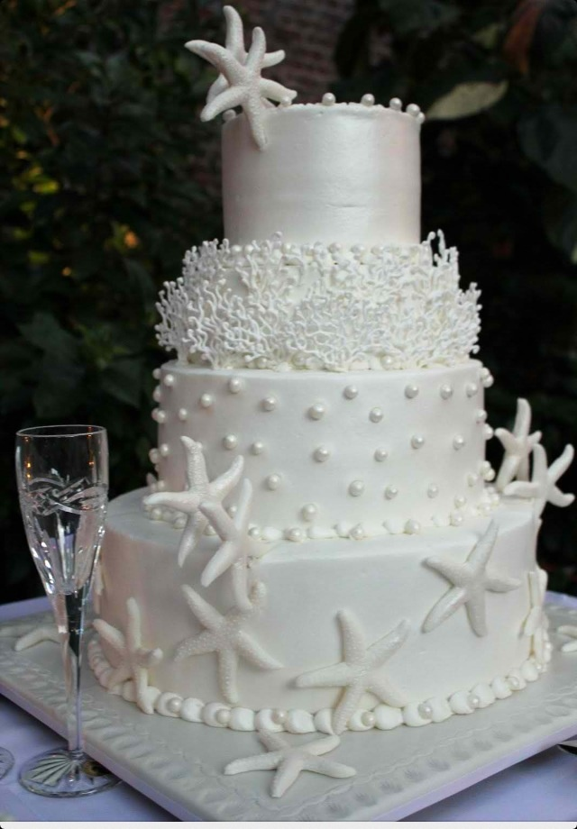 a white shimmering wedding cake decorated with edible pearls, corals, starfish and pearls and starfish on top is very elegant