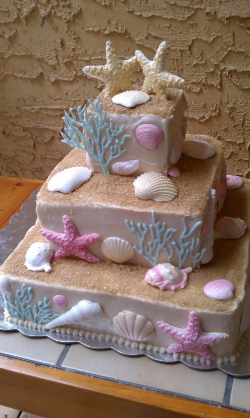 a catchy blush square wedding cake with beach sand, seashells, corals and starfish of sugar in various colors