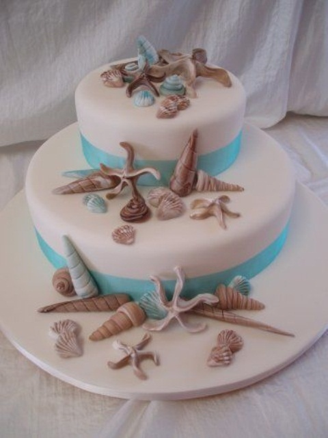an elegant white wedding cake with turquoise ribbons, sugar seashells and starfish is a lovely modern wedding idea