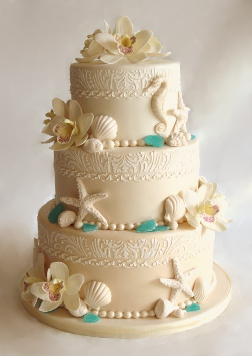 a refined neutral wedding cake with various patterns, orchids, sea glass and seashells, starfish and sea horses of sugar