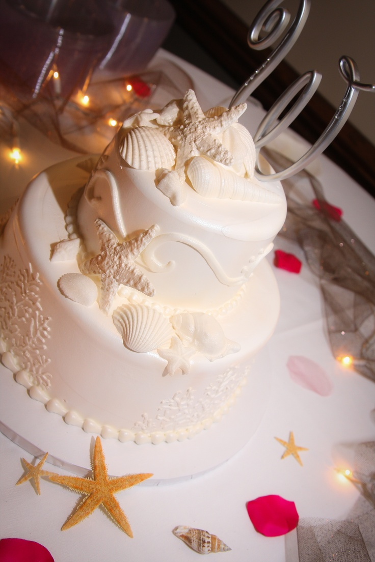 a white beach wedding cake with coral patterns, sugar seashells and starfish on top for an elegant beach wedding